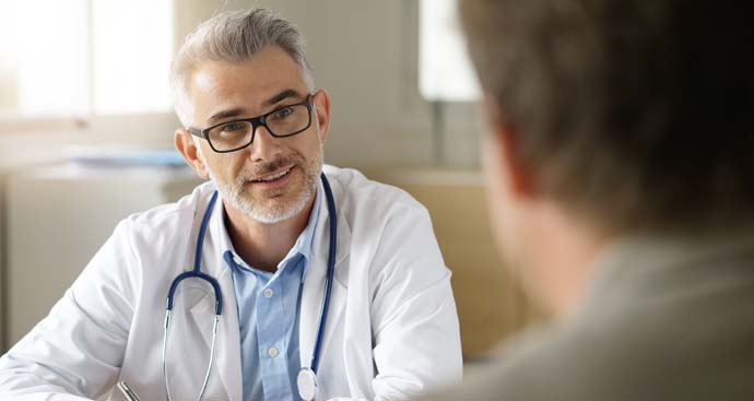a weight loss doctor wearing dark framed glasses talks to a patient in his office about losing weight