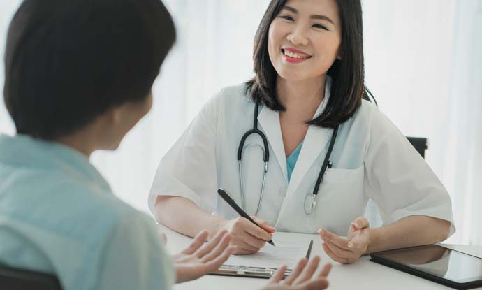 a female doctor smiling as she talks to patient about starting a weight loss program at the clinic