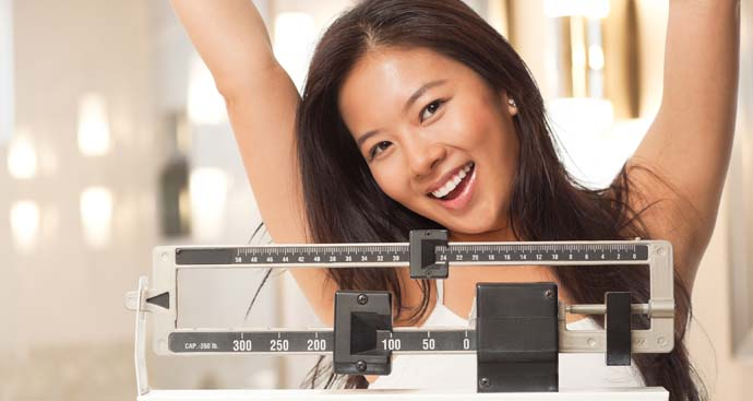 woman on scale with arms in the arm smiling and happy after losing weight