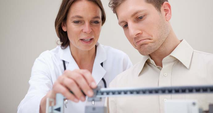 doctor weight a male patient on a scale and talking about his weight as she adjusts the scale