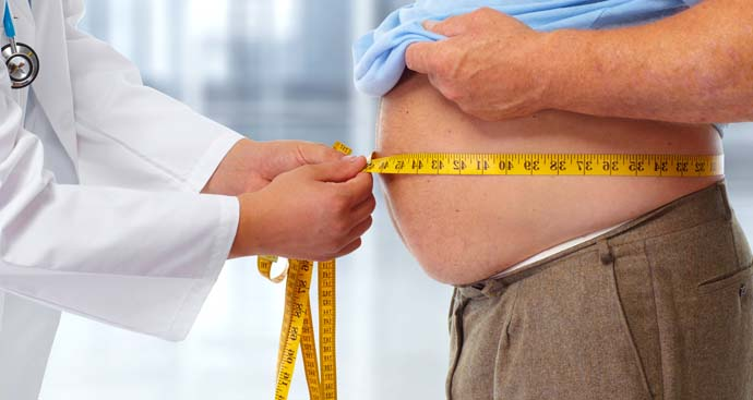 close up image of a man's large stomach and the hands of a doctor measuring his waist