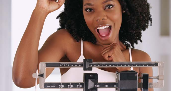 woman with hand in the air happy about her weight loss